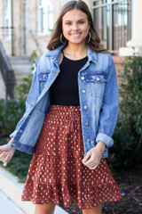 Model wearing the Rust Metallic Polka Dot Tiered Skirt with black bodysuit and distressed denim jacket from Dress Up Front View