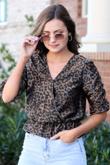Model wearing the Draped Sleeve Leopard Blouse with high rise jeans and sunglasses from Dress Up Front View