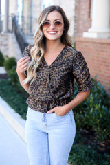 Model wearing the Draped Sleeve Leopard Blouse with high rise jeans and sunglasses from Dress Up