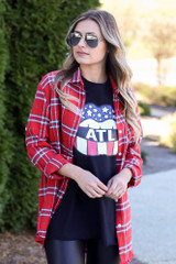 Model wearing the Atlanta Graphic Tee with flannel and faux leather leggings from Dress Up