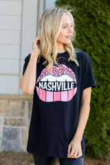 Model wearing the Black Nashville Graphic Tee in Large with leggings from Dress Up Side View