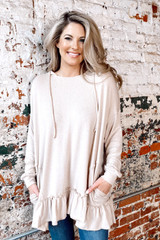 Model wearing the Ruffle Hem Hoodie in Taupe with jeans