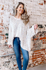Model wearing the Chenille Confetti Knit Oversized Top in Ivory with high rise jeans from Dress Up