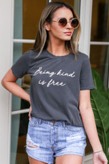 Dress Up model wearing the Kindness is Free Graphic Tee with light wash denim shorts and circular sunglasses