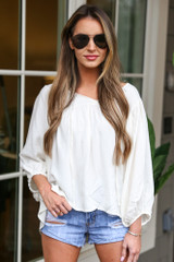Dress Up model wearing the Balloon Sleeve Babydoll Blouse with light wash distressed denim shorts and aviator sunglasses