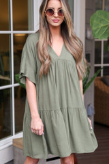 Model wearing the Tiered Babydoll Dress in Olive with circular sunglasses