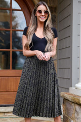 Model wearing the Leopard Pleated Midi Skirt with a black bodysuit and circular sunglasses
