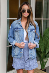 Dress Up model wearing the Distressed Denim Jacket with a blue floral wrap skirt