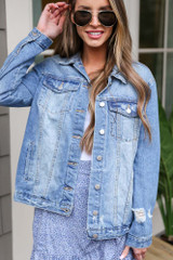 Model wearing the Distressed Denim Jacket in Medium Wash with aviator sunglasses