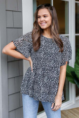 Dress Up model wearing the Spotted Tiered Babydoll Top with light wash jeans and aviator sunglasses