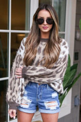 Model wearing the High-Waisted Distressed Mom Shorts with a leopard sweater