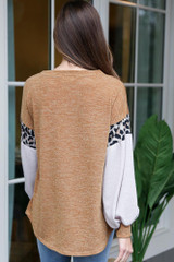 Model wearing the Mustard Statement Sleeve Knit Top with high rise jeans and booties from Dress Up Back View