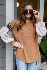 Model wearing the Mustard Statement Sleeve Knit Top with high rise jeans and booties from Dress Up Side View