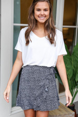 Model wearing the Floral Wrap Skirt in Black with white tee from Dress Up Boutique Front View