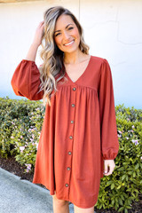 Dress Up model wearing the V-Neck Button Front Babydoll Dress in Rust