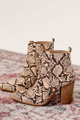 Flat Lay of the Pointed Toe Block Heel Booties in snake on oriental rug from online dress boutique