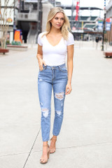 Model wearing the High-Rise Distressed Mom Jeans with a white bodysuit