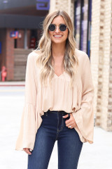 Model wearing the Bell Sleeve Babydoll Blouse tucked into dark wash jeans