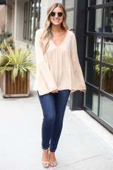 Dress Up model wearing the Bell Sleeve Babydoll Blouse with dark wash jeans and nude heels