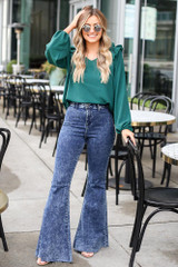 Dress Up model wearing the Ruffle Shoulder Blouse with flare jeans