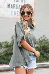 Model wearing the Cowl Neck Oversized Knit Top in Olive twirling