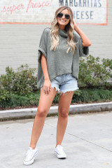 Dress Up model wearing the Cowl Neck Oversized Knit Top in Olive with denim shorts and white sneakers