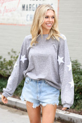 Dress Up model wearing the Star Sleeve Oversized Pullover in Heather Grey tucked into denim shorts