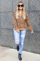 Model wearing the Camel V Neck Leopard Luxe Knit Top with distressed jeans and block heel booties