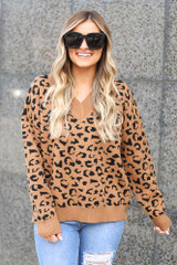 Model wearing the Camel V Neck Leopard Luxe Knit Top with distressed jeans and sunglasses