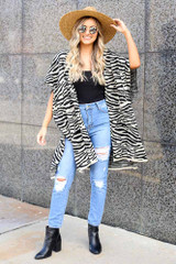 Model wearing the Zebra Knit Shawl Cardigan with a wide brim hat and a black lace tank