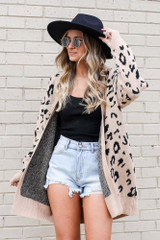 Model wearing the Taupe Leopard Print Luxe Knit Cardigan with wide brim fedora and denim shorts Front View
