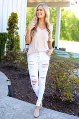 Model wearing the High-Rise Button Front Distressed White Jeans with a v-neck  tee and nude mules