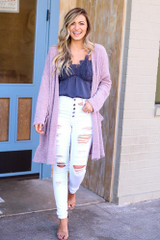 Model wearing the Blush Fuzzy Knit Cardigan with high rise white distressed jeans