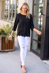 Model wearing the Scalloped Open Back Blouse in Black with distressed white jeans