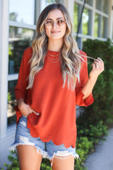 Dress Up model wearing the Scalloped Open Back Blouse with distressed denim shorts