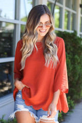 Rust - Model wearing the Scalloped Open Back Blouse with dark wash jeans