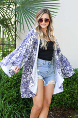 Model wearing the Bell Sleeve Printed Kimono with denim shorts and tank top from Dress Up Boutique