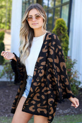 Model wearing the Luxe Knit Leopard Ruffle Cardigan with high rise distressed jeans and white tank from Dress Up Side View