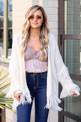 Model wearing the Fringe Knit Cardigan with a lace tank and dark wash jeans