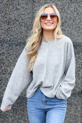 Model wearing the Ribbed Knit Oversized Top in Grey with high rise jeans