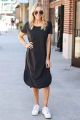 Model wearing the Jersey Knit Midi Dress in Black with white sneakers