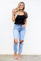 Model wearing the Puff Sleeve Smocked Crop Top with high rise distressed boyfriend jeans from Dress Up