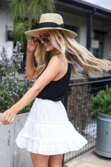 Model wearing the Eyelet Tiered Skirt in white with black tank top and wide brim fedora