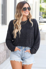 Dress Up model wearing the Lightweight Ribbed Knit Oversized Top in Black with denim shorts and sunglasses
