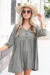 Model wearing the Button Front Babydoll Dress in Olive with gold jewelry and trendy shoes from Dress up boutique