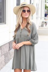 Model wearing the Button Front Babydoll Dress in Olive with trendy shoes and cute accessories from trendy online dress boutique Front View