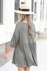 Model wearing the Button Front Babydoll Dress in Olive with trendy accessories from DresS Up Boutique Back View