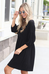 Model wearing the Button Front Babydoll Dress in Black with wide brim fedora from Dress Up Boutique Side View