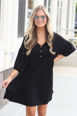 Model wearing the Button Front Babydoll Dress in black with trendy accessories and polarized aviator sunglasses from trendy online boutique