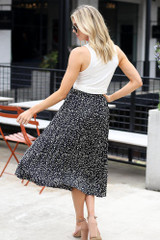 Model wearing the Spotted Pleated Midi Skirt in Black Back view